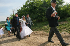 Gypsy wedding. Mociu commune, Cluj-Napoca, Romania, June 6, 2009: A bride and a groom from a gypsy family, accompanied by their guest are passing on the street stock photo