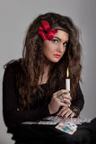 Gypsy woman. With a candle and fortune predicting cards royalty free stock image