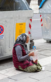 Gypsy woman ask money. Gypsy beggar on the streets of Trieste with a plastic cup asking for money royalty free stock image