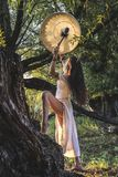 Gypsy woman in the forest drumming Stock Images