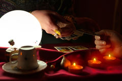 Gypsy woman fortune teller giving tarot card to another woman. For future reading Stock Photography