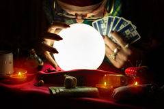 Gypsy woman looking at crystal ball and holding a tarot cards Stock Images