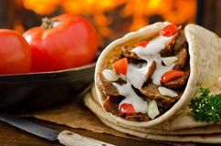 Gyro Donair. A spicy Gyro Donair with tomatoes and parsley against a hardwood fire background Stock Photos
