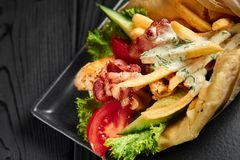 Gyro in pita with bacon, chicken and tzatziki. Greek cuisine dish. healthy fast food. Close up. Gyro in pita with bacon, chicken and tzatziki. Traditional Greek royalty free stock photos