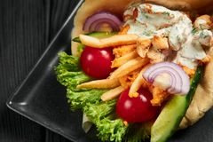 Gyro in pita with chicken, vegetables and tzatziki. Greek cuisine dish. healthy fast food. Close up. Gyro in pita with chicken, vegetables and tzatziki stock photos