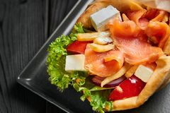 Gyro in pita with salmon fish, vegetables and feta. Traditional Greek cuisine dish. healthy lunch. At black wooden backdrop. Close up royalty free stock photo