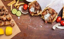 Gyro pita, shawarma, souvlaki. Two pita bread wraps and meat skewers on wooden table stock image