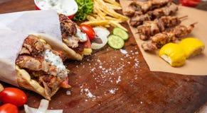Gyro pita, shawarma, souvlaki. Two pita bread wraps and meat skewers on wooden table. Gyro pita, shawarma, souvlaki. Traditional turkish, greek meat food. Two royalty free stock photo