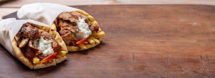 Gyro pita, shawarma, take away, street food. Traditional greek turkish, meat food on wooden table. Gyro pita, shawarma, take away, street food. Two pita bread stock photography