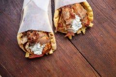 Gyro pita, shawarma, take away, street food. Traditional greek turkish, meat food on wooden table. Gyro pita, shawarma, take away, street food. Two pita bread stock images