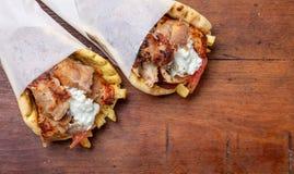 Gyro pita, shawarma, take away, street food. Traditional greek turkish, meat food on wooden table. Gyro pita, shawarma, take away, street food. Two pita bread royalty free stock images