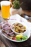 Gyro plate with meat on a pita. Gyro plate with rotisserie meat on a pita and vegetables with a glass of beer royalty free stock image