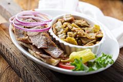 Gyro plate with meat on a pita. Gyro plate with rotisserie meat on a pita and vegetables with a glass of beer royalty free stock photography