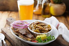 Gyro plate with meat on a pita. Gyro plate with rotisserie meat on a pita and vegetables with a glass of beer stock images