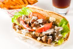 Gyro Sandwich with Fries and Cola. Fresh traditional gyro sandwich with lamb, feta cheese, tomato lettuce and dressing stock image