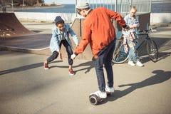 Gyroboard élégant d'équitation de garçon de hippie avec des amis tout près Photos stock