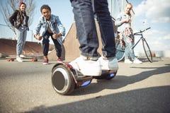 Gyroboard élégant d'équitation de garçon de hippie avec des amis tout près Image stock