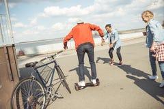 Gyroboard élégant d'équitation de garçon de hippie avec des amis tout près Photo stock