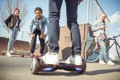 Gyroboard élégant d'équitation de garçon de hippie avec des amis tout près Images stock