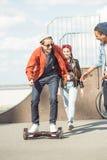 Gyroboard d'équitation d'adolescent avec des amis tout près, concept de style de hippie Images libres de droits