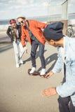 Gyroboard d'équitation d'adolescent avec des amis tout près, concept de style de hippie Image libre de droits