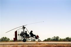 Gyrocopter silhouette. A  two person gyrocopter, in silhouette, as it prepares to take off. Figures backlit for effect Royalty Free Stock Photo