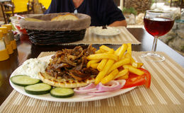 Gyros dinner. Plate of traditional  Gyros with french fries on table of a outdoor greek restaurant Royalty Free Stock Images