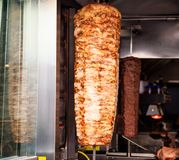 Gyro or doner roasted slowly on rotating spit. Close up view. Gyros, doner grilled slowly on rotating spit. Blurred background royalty free stock image