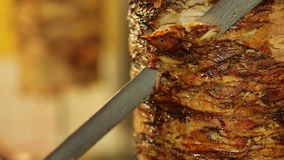 Gyros meat. A cook cuts meat to make shawarma, gyros, doner kebab. Cooking meat on a skewer stock video footage