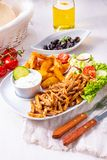 Gyros plate it green salad ,olives and potato wedges royalty free stock photos