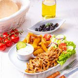 Gyros plate it green salad ,olives and potato wedges stock photography