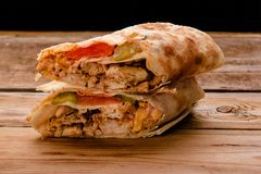 Gyros souvlaki wrapped in a pita bread on a wooden background royalty free stock photography