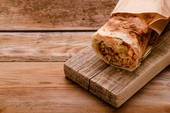 Gyros souvlaki wrapped in a pita bread on a wooden background stock photo