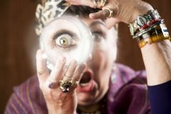 Gyspy with a crystal ball. Female gypsy fortune teller holding a crystal ball to her eye Royalty Free Stock Images