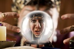 Gyspy seen in a crystal ball. Female gypsy fortune teller looking into a crystal ball Stock Photo