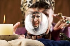 Gyspy seen in a crystal ball. Female gypsy fortune teller looking into a crystal ball Stock Photography