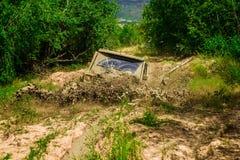 Gyttja- och vattenfärgstänk, i av-väg att springa Mudding off-roading till och med ett område av våt gyttja eller lera Spår på et royaltyfri fotografi