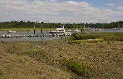 Gyttjalägenheterna på sköldar hårt på den Beaulieu floden i Hampshire, England på lågvatten med fartyg på deras förtöjning royaltyfri foto
