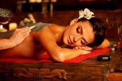 Gyttjamaskering av kvinnan i brunnsortsalong tillbaka massage fotografering för bildbyråer