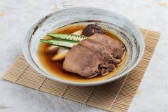 Gyutan fluida del tounge de la carne de vaca servida con el shiitake, la cebolleta japonesa y chiles con la sopa en placa de pied Foto de archivo