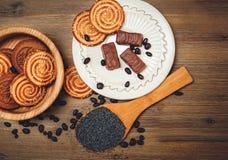 Há cookies, doces, ervilhas do chocolate, papoila; Pires da porcelana, alimento doce saboroso no fundo de madeira Fotos de Stock Royalty Free