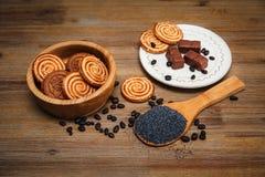 Há cookies, doces, ervilhas do chocolate, papoila; Placa cerâmica; Alimento doce saboroso Fotos de Stock