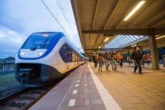 Há passageiros perto do trem em uma plataforma railway Imagens de Stock