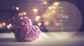Há sempre uma razão sorrir mensagem com um coração cor-de-rosa Fotos de Stock