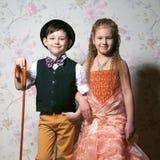 Há um retrato da menina e do menino de sorriso nos vagabundos florais Imagem de Stock