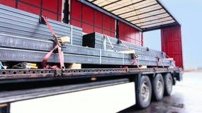 Há uma carga ao reboque do caminhão asseguração do frete no reboque foto de stock