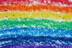 Há umas gotas da água que gotejam sobre um arco-íris com pastéis foto de stock royalty free