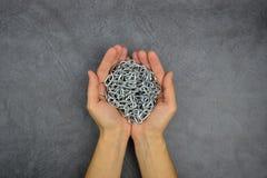 Há umas mãos que guardam uma corrente de prata do metal no fundo cinzento Imagem de Stock