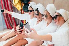Hábito de la relajación de la diversión de las muchachas de la albornoz del tiempo de Selfie foto de archivo