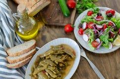 Hábitos alimentarios sanos, aceite de oliva con la comida de la haba y ensalada y imagenes de archivo